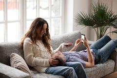 Εύθυμη νέα χαλάρωση ζευγών στον καναπέ που μιλά και που κρατά έξυπνος στοκ εικόνα