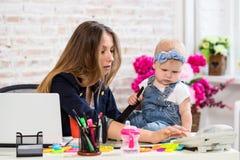 Εύθυμη νέα όμορφη επιχειρηματίας που εξετάζει το τηλέφωνο καθμένος στη θέση εργασίας της με την λίγη κόρη Στοκ Εικόνες