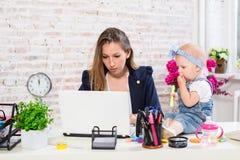 Εύθυμη νέα όμορφη επιχειρηματίας που εξετάζει το lap-top καθμένος στη θέση εργασίας της με την λίγη κόρη Στοκ Εικόνες
