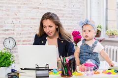 Εύθυμη νέα όμορφη επιχειρηματίας που εξετάζει το lap-top καθμένος στη θέση εργασίας της με την λίγη κόρη Στοκ εικόνες με δικαίωμα ελεύθερης χρήσης