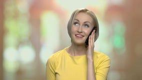 Εύθυμη ξανθή γυναίκα που μιλά στο τηλέφωνο κυττάρων φιλμ μικρού μήκους