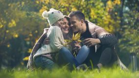 Εύθυμη οικογένεια που αγκαλιάζει ηλικίας τη σχολείο κόρη στο πάρκο φθινοπώρου, τέλειο Σαββατοκύριακο φιλμ μικρού μήκους
