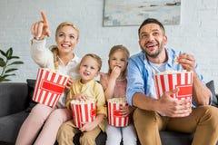 εύθυμη οικογένεια που τρώει popcorn και που προσέχει τη TV από κοινού στοκ φωτογραφίες με δικαίωμα ελεύθερης χρήσης