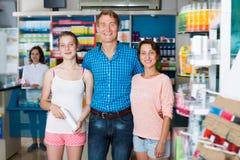 Εύθυμη οικογένεια τριών που στέκονται στο φαρμακείο στοκ εικόνες με δικαίωμα ελεύθερης χρήσης