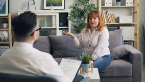 Εύθυμη παχύσαρκη γυναίκα που μιλά στον αρσενικό ψυχολόγο στην κλινική κατά τη διάρκεια της συνόδου απόθεμα βίντεο