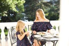 Εύθυμη συνεδρίαση μητέρων και κορών υπαίθρια στον καφέ ενώ drin Στοκ φωτογραφία με δικαίωμα ελεύθερης χρήσης
