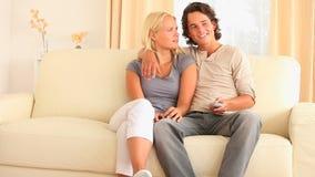 Εύθυμη συνεδρίαση ζευγών σε έναν καναπέ που προσέχει τη TV απόθεμα βίντεο