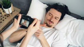 Εύθυμη τοποθέτηση νεαρών άνδρων στο σπίτι στο κρεβάτι ενώ κορίτσι που χρησιμοποιεί τη σύγχρονη κάμερα απόθεμα βίντεο