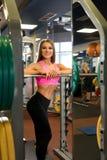 Εύθυμη φίλαθλος που στέκεται κοντά barbells στη γυμναστική στοκ εικόνες