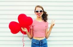 Εύθυμη χαμογελώντας γυναίκα πορτρέτου με τη μορφή καρδιών μπαλονιών αέρα που έχει τη διασκέδαση πέρα από το λευκό Στοκ φωτογραφία με δικαίωμα ελεύθερης χρήσης