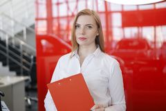 Εύθυμη χαριτωμένη ξανθή στάση στο γραφείο που κρατά έναν φάκελλο στα χέρια της και που κοιτάζει μακριά στοκ φωτογραφία με δικαίωμα ελεύθερης χρήσης