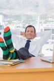 Εύθυμη χαλάρωση επιχειρηματιών με τα πόδια στο γραφείο του Στοκ Φωτογραφία