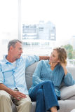 Εύθυμη χαλάρωση ζευγών στον καναπέ τους που έχει μια συνομιλία στοκ φωτογραφίες με δικαίωμα ελεύθερης χρήσης