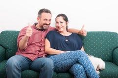 Εύθυμη χαλάρωση ζευγών στο σπίτι με το χαριτωμένο bichon Στοκ εικόνες με δικαίωμα ελεύθερης χρήσης