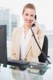 Εύθυμη όμορφη επιχειρηματίας που απαντά στο τηλέφωνο Στοκ Φωτογραφία