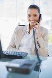 Εύθυμη όμορφη επιχειρηματίας που απαντά στο τηλέφωνο Στοκ Εικόνα