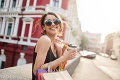 Εύθυμη όμορφη καυκάσια νέα γυναίκα με τη σκοτεινή τρίχα στα γυαλιά ήλιων και το μαύρο φόρεμα που χαμογελά λαμπρά, που κοιτάζει μέ Στοκ φωτογραφία με δικαίωμα ελεύθερης χρήσης