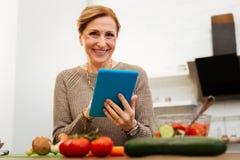 Εύθυμη όμορφη κυρία με το δεμένο χρόνο εξόδων τρίχας στην κουζίνα στοκ εικόνες