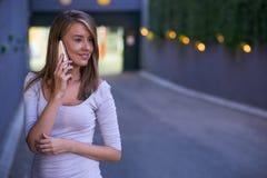 Εύθυμη όμορφη συνεδρίαση γυναικών στα σκαλοπάτια και ομιλία στο κινητό τηλέφωνο Στοκ Φωτογραφίες