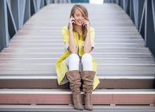 Εύθυμη όμορφη συνεδρίαση γυναικών στα σκαλοπάτια και ομιλία στο κινητό τηλέφωνο Στοκ Εικόνες