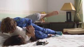 Εύθυμοι αδελφοί χαράς στις πυτζάμες σε μια κρεβατοκάμαρα Δύο τύποι που παίζουν γύρω στο κρεβάτι με τα μαξιλάρια brow φιλμ μικρού μήκους