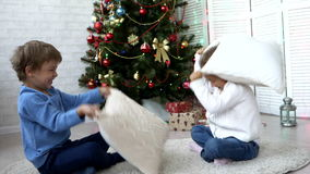 Εύθυμοι αμφιθαλείς που παλεύουν με τα μαξιλάρια στο σπίτι δίπλα στο χριστουγεννιάτικο δέντρο απόθεμα βίντεο