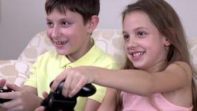 Εύθυμοι αδελφός και αδελφή που παίζουν τα τηλεοπτικά παιχνίδια στον καναπέ στο σπίτι απόθεμα βίντεο