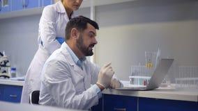 Εύθυμοι επιστήμονες που εργάζονται στο lap-top από κοινού φιλμ μικρού μήκους