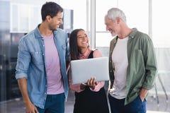 Εύθυμοι επιχειρηματίες με το lap-top Στοκ Φωτογραφία