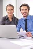 Εύθυμοι επιχειρηματίες που κάθονται στον πίνακα με το lap-top Στοκ Εικόνες
