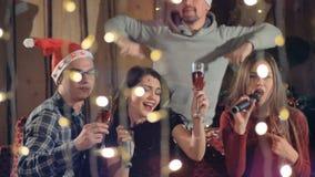 Εύθυμοι ευτυχείς φίλοι με το ποτήρι της σαμπάνιας που έχει τη διασκέδαση στη γιορτή Χριστουγέννων απόθεμα βίντεο