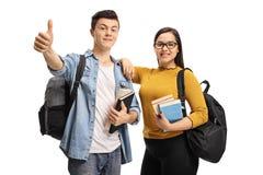 Εύθυμοι εφηβικοί σπουδαστές με το σακίδιο πλάτης και βιβλία που κάνουν έναν αντίχειρα Στοκ Φωτογραφίες