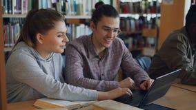Εύθυμοι θηλυκοί και αρσενικοί φοιτητές πανεπιστημίου που εργάζονται στο lap-top μαζί καθμένος στον πίνακα στην πανεπιστημιακή βιβ φιλμ μικρού μήκους