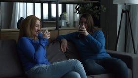 Εύθυμοι θηλυκοί φίλοι που ψήνουν τα γυαλιά κρασιού στον καναπέ φιλμ μικρού μήκους