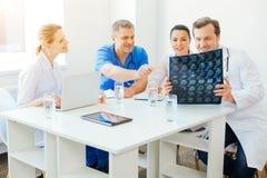 Εύθυμοι ιατρικοί επαγγελματίες που συμβουλεύουν πέρα από την εικόνα ανίχνευσης MRI στην εργασία στοκ φωτογραφίες