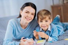 Εύθυμοι μητέρα και γιος που θέτουν κάνοντας τις σημειώσεις Στοκ Εικόνα