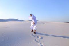 Εύθυμοι μουσουλμανικοί περίπατοι τύπων μέσω των εκτάσεων της ερήμου με το χαμόγελο Στοκ φωτογραφία με δικαίωμα ελεύθερης χρήσης