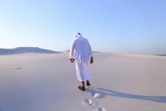 Εύθυμοι μουσουλμανικοί περίπατοι τύπων μέσω των εκτάσεων της ερήμου με το χαμόγελο Στοκ Εικόνες