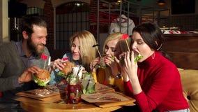Εύθυμοι νέοι που τρώνε burger και που απολαμβάνουν σε ένα εστιατόριο γρήγορου φαγητού απόθεμα βίντεο
