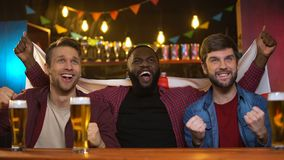 Εύθυμοι πολυφυλετικοί ανεμιστήρες ενθαρρυντικοί για τη ομάδα ποδοσφαίρου, κυματίζοντας αγγλική σημαία, χόμπι απόθεμα βίντεο