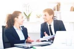 Εύθυμοι συνάδελφοι νεαρών άνδρων και γυναικών που μιλούν στο σταθερό γραφείο στοκ εικόνα
