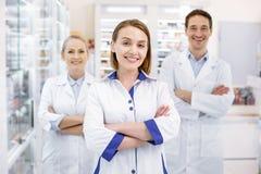 Εύθυμοι τρεις φαρμακοποιοί που περιμένουν τους πελάτες στοκ εικόνες