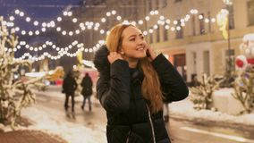 Εύθυμοι χοροί γυναικών υπαίθρια κάτω από την πτώση χιονιού Η ευτυχής κυρία βάζει την κουκούλα με τη γούνα σε την και χαμόγελα απόθεμα βίντεο