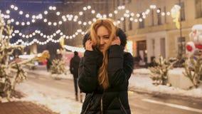 Εύθυμοι χοροί γυναικών υπαίθρια κάτω από την πτώση χιονιού Η ευτυχής κυρία βάζει την κουκούλα με τη γούνα σε την και χαμόγελα φιλμ μικρού μήκους