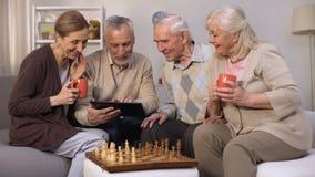 Εύθυμοι ώριμοι φίλοι που διαβάζουν τους κανόνες παιχνιδιών σκακιού για την ταμπλέτα, που εξετάζει τη κάμερα απόθεμα βίντεο