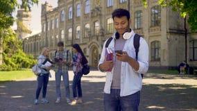 Εύθυμος άνδρας σπουδαστής που χρησιμοποιεί κινητό app στο smartphone, που ψάχνει την εργασία on-line φιλμ μικρού μήκους