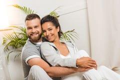 Εύθυμος άνδρας που αγκαλιάζει τη γυναίκα και που εξετάζει τη κάμερα Στοκ Εικόνες