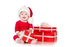 Εύθυμος λίγος Άγιος Βασίλης με παρουσιάζει. Στοκ Φωτογραφία