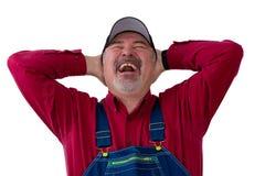 Εύθυμος αγρότης ή εργαζόμενος που απολαμβάνει ένα εγκάρδιο γέλιο Στοκ Φωτογραφίες