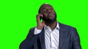 Εύθυμος αμερικανικός επιχειρηματίας afro που μιλά στο τηλέφωνο απόθεμα βίντεο